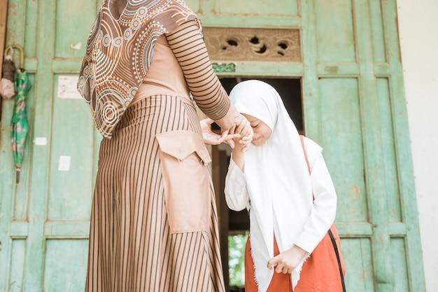 Aluna muçulmana aperta e beija a mão de sua mãe antes de ir para a escola pela manhã