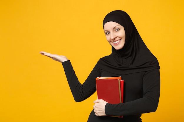 Aluna muçulmana árabe em roupas pretas de hijab contém livros isolados no retrato de parede amarela. estilo de vida religioso de pessoas, educação no conceito de ensino médio. .