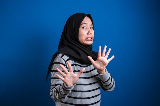 Aluna muçulmana asiática fazendo gesto de parada, contra um fundo azul. pare de fazer bullying com ela