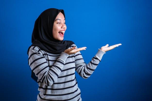 Aluna muçulmana asiática sorrindo e apontando para apresentar algo do lado dela com espaço de cópia
