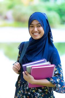 Aluna muçulmana com retrato de livros