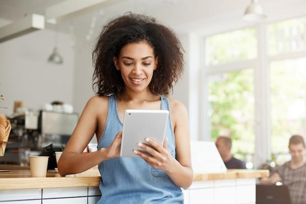 Aluna muito africana descansando no café sorrindo olhando para a tela do tablet.