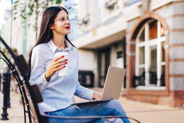 Aluna muito sorridente, vestida de maneira casual, sentada ao ar livre em um banco, tomando café e trabalhando, usando um laptop