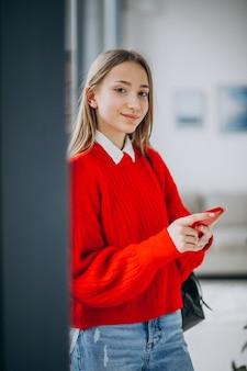 Aluna na camisola vermelha usando o telefone