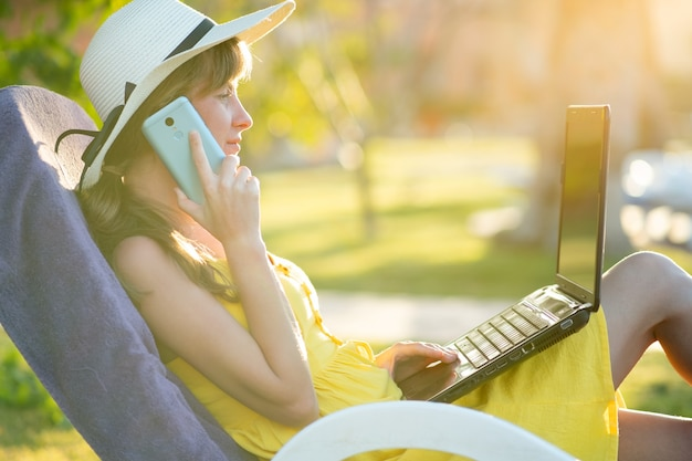 Aluna no vestido amarelo do verão que descansa no gramado verde no parque do verão que estuda no portátil do computador que tem a conversa no telefone celular móvel. fazendo negócios e aprendendo durante o conceito de quarentena.