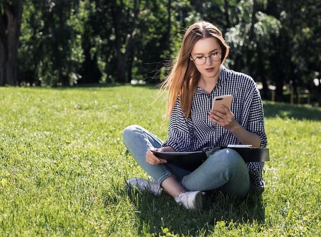 Aluna olha para seu smartphone com uma pasta nas mãos dela, sentado na grama do parque