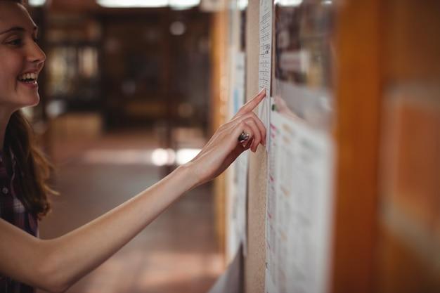 Aluna olhando para um quadro de avisos no corredor