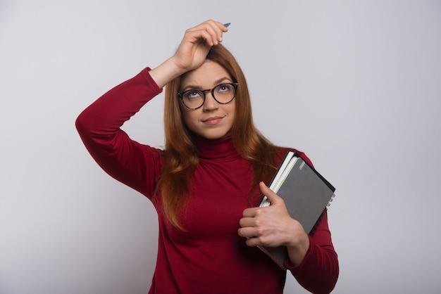 Aluna pensativa com livros didáticos e caneta