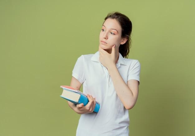 Aluna pensativa, jovem e bonita segurando um livro e um bloco de notas, olhando para o lado e tocando o rosto isolado em um fundo verde oliva com espaço de cópia