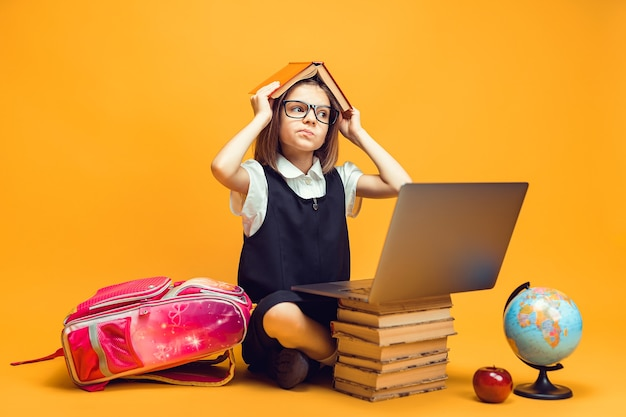 Aluna pensativa sentada atrás de uma pilha de livros e um laptop segurando um livro sobre a educação dos filhos.
