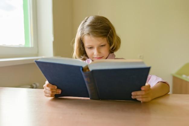 Aluna pequena senta-se em uma mesa com livro