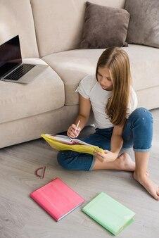 Aluna pré-adolescente bonita positiva fazendo lição de casa com o laptop em casa