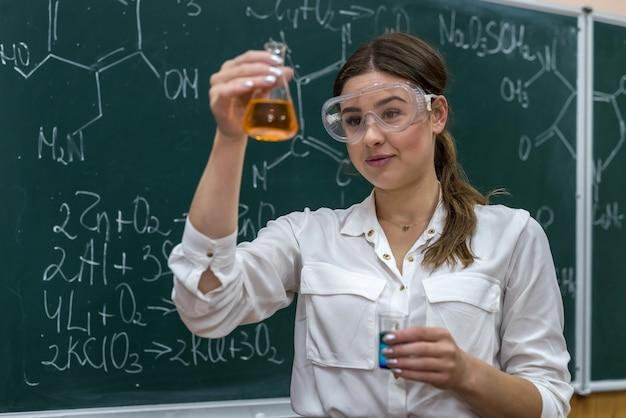 Aluna realiza experiência em aula de química segurando um líquido colorido no frasco