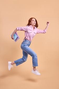 Aluna ruiva emocional correndo para frente com um livro nas mãos, corre para a universidade, vestindo roupa casual, correndo, prova de 1º de setembro, isolada no estúdio, retrato de corpo inteiro