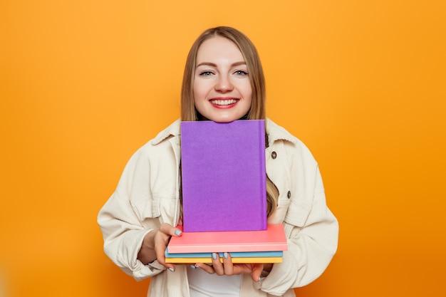 Aluna segurando muitos livros nas mãos, isolados sobre o fundo laranja do estúdio
