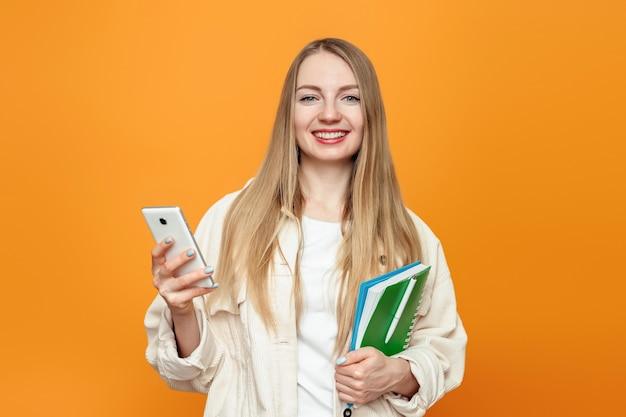 Aluna segurando um celular e um bloco de notas, olhando para a câmera e sorrindo