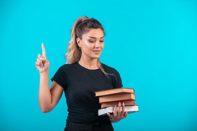 Aluna segurando um grande estoque de livros e tem uma ideia.