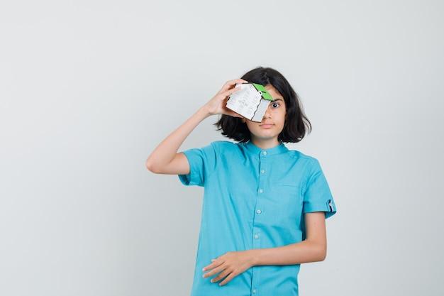 Aluna segurando um modelo de casa sobre os olhos em uma camisa azul