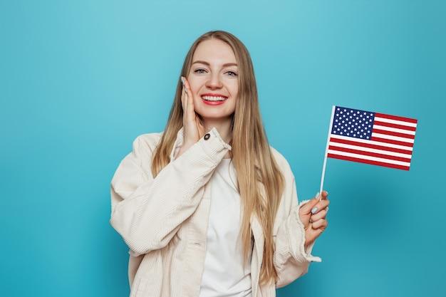 Aluna segurando uma pequena bandeira americana e sorrindo