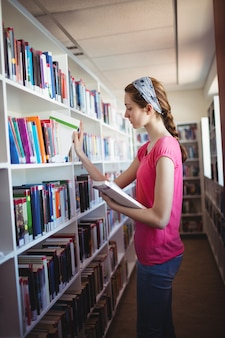 Aluna selecionando um livro da estante de livros na biblioteca