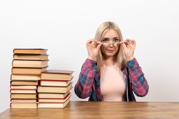 Aluna sentada com diferentes livros em branco