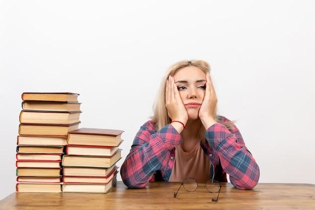 Aluna sentada com livros diferentes, cansada no branco