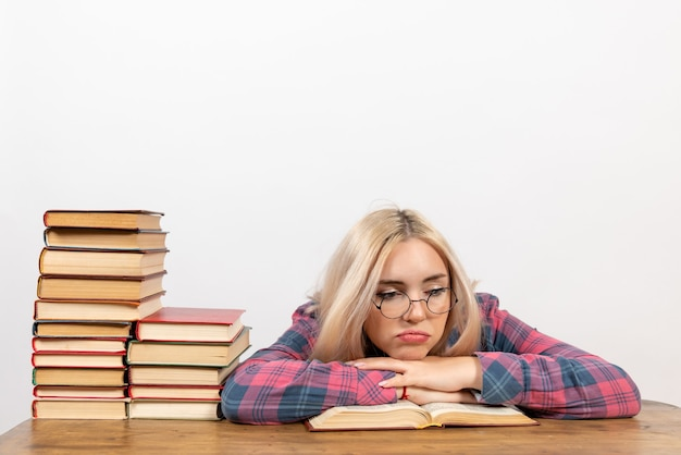 Aluna sentada com livros se sentindo cansada em branco