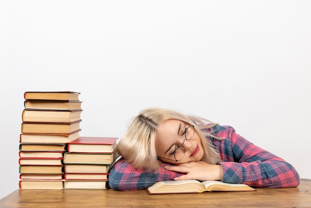 Aluna sentada com livros, sentindo-se cansada e dormindo no branco