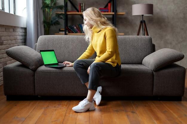 Aluna sentada no sofá segurando um laptop olhando para a tela simulada