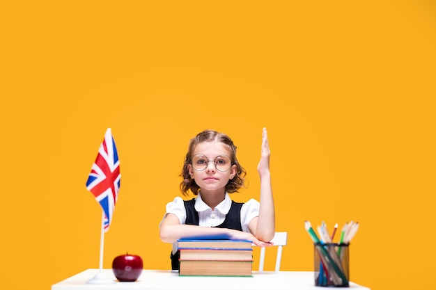 Aluna séria caucasiana sentada à mesa e levantando a mão na aula de inglês, bandeira da grã-bretanha