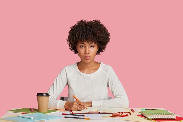 Aluna séria e concentrada posando na mesa contra a parede rosa