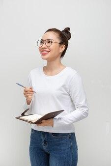 Aluna séria e pensativa lendo suas anotações, segurando uma caneta e um caderno aberto