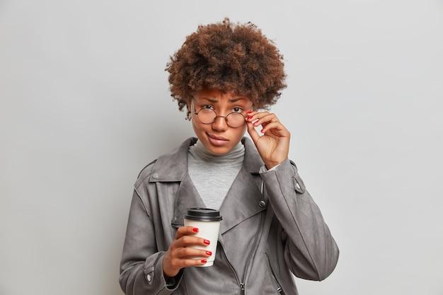 Aluna séria olha com segurança através de óculos transparentes, ouve com atenção o intercolutor, bebe café para viagem, vestida com jaqueta cinza