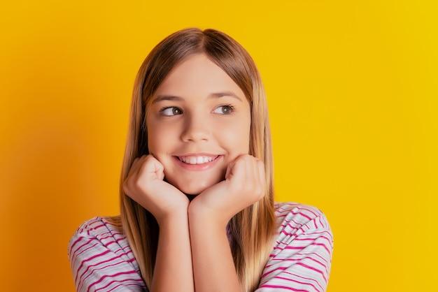 Aluna sonhadora tocando as maçãs do rosto mãos parecem um espaço vazio fundo amarelo vibrante