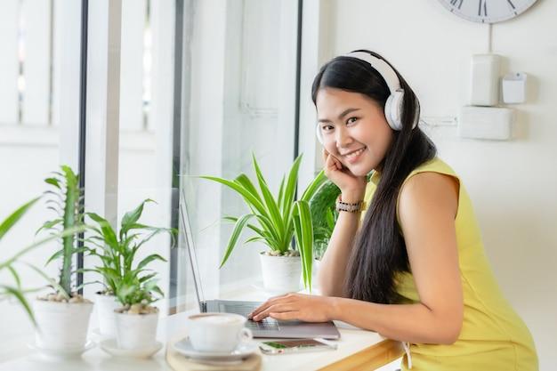 Aluna sorridente asiática usa estudo de fone de ouvido sem fio on-line com o professor do skype em uma cafeteria