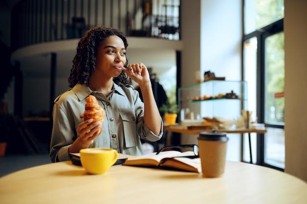 Aluna sorridente bebe café com croissants no café. mulher aprendendo um assunto em cafeteria, educação e comida. menina estudando na cafeteria do campus