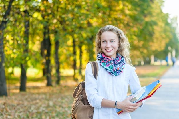 Aluna sorridente com pastas e livros andando no outono