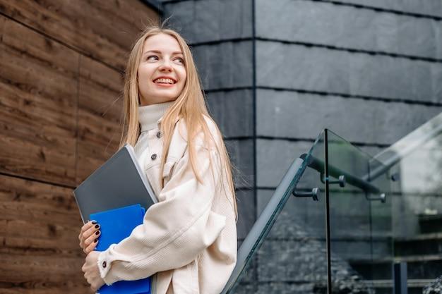 Aluna sorridente contém pastas, livros de cadernos em sorrisos de mãos, desvia o olhar contra um edifício de universidade moderna. copie o espaço