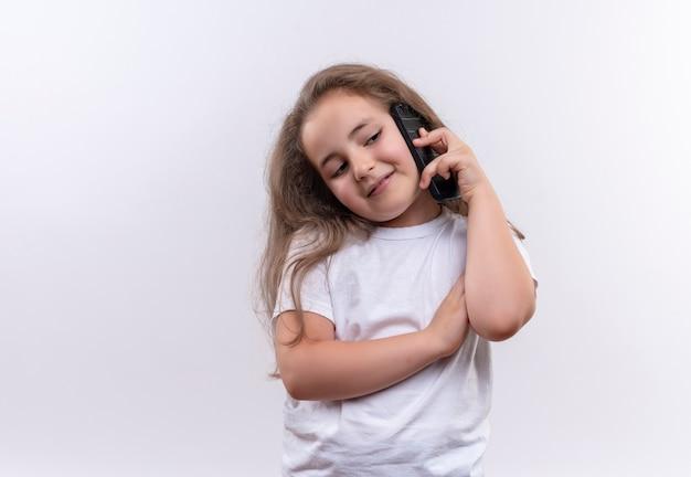 Aluna sorridente de camiseta branca fala ao telefone sobre fundo branco isolado