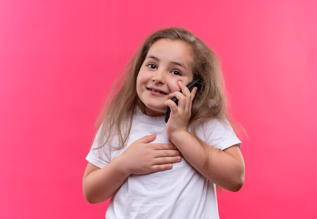 Aluna sorridente de camiseta branca fala ao telefone sobre fundo rosa isolado