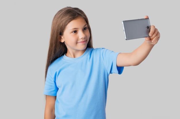 Aluna sorridente em camiseta azul tomando selfie com grande smartphone moderno cinza