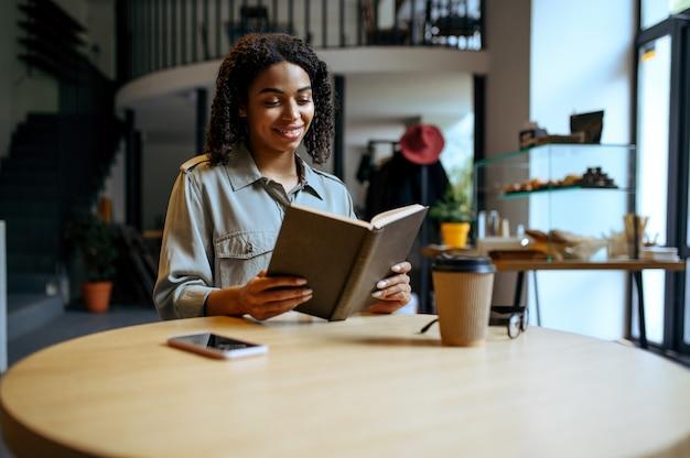 Aluna sorridente lê um livro no café. mulher aprendendo um assunto em cafeteria, educação e comida. menina estudando na cafeteria do campus