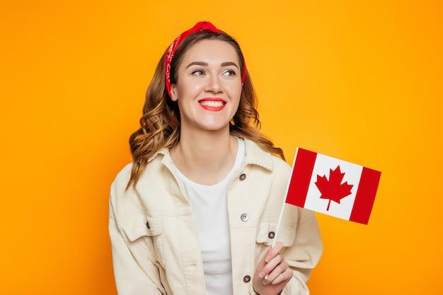 Aluna sorrindo e segurando uma pequena bandeira do canadá isolada sobre fundo laranja