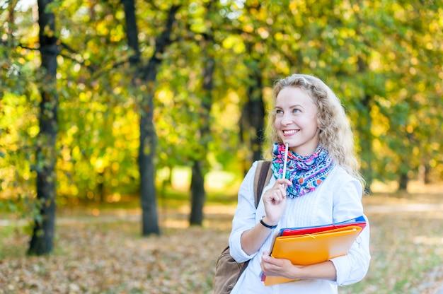 Aluna sorrindo e segurando uma pilha de pastas no outono
