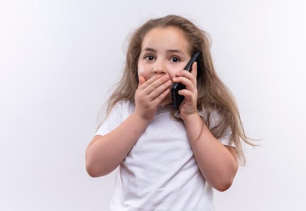 Aluna surpresa com camiseta branca fala no telefone com a boca coberta em um fundo branco isolado