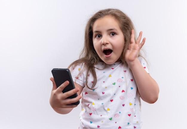 Aluna surpresa com camiseta branca segurando o telefone, mostrando gesto de escuta