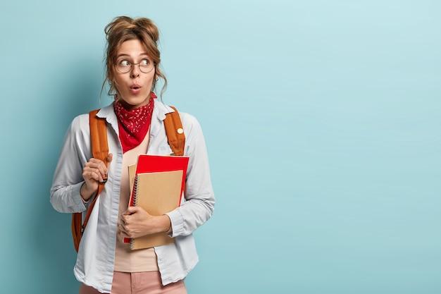 Aluna surpresa com mochila, segurando um bloco de notas em espiral, livro vermelho, chocada com a sessão na próxima semana, usa óculos redondos
