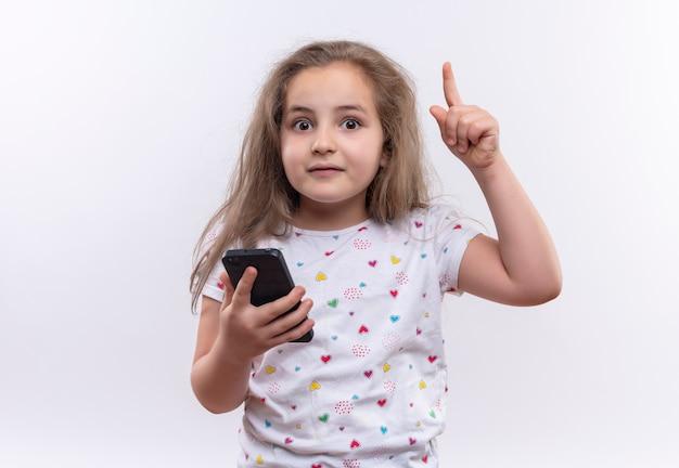 Aluna surpresa com uma camiseta branca segurando o telefone apontando para cima em um fundo branco isolado