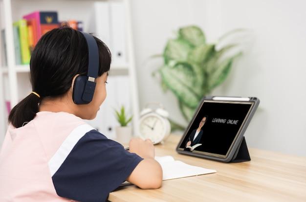 Aluna tailandesa asiática aprendendo on-line em um tablet em casa, criança estudando e trabalhando feliz durante o confinamento por causa de covid 19 ou coronavírus