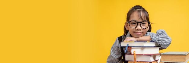 Aluna tailandesa asiática cai sobre um livro empilhado, usando óculos e olhando a câmera no estúdio em laranja ou amarelo